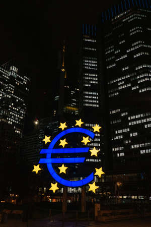 FRANKFURT-AM-MAIN, GERMANY - MARCH 2020: Illuminated buildings of the European Central Bank and Euro sign at night in Frankfurt, Germany