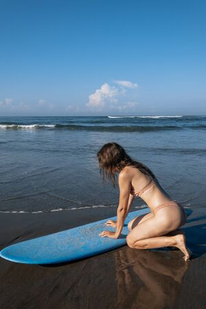Sensual young brunette woman with blue surfboard sitting on beach.Side view of girl prepare to surfing. Extreme sport and vacation concept Imagens