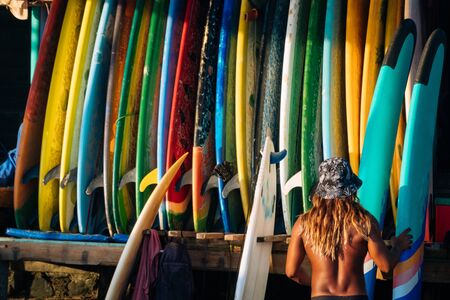 Set of different color surf boards in a stack by ocean with unrecognizable man choosing board. Bali.Indonesia. Surf boards on sandy beach for rent. Surf lessons on Weligama beach, Sri Lanka. Фото со стока