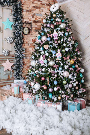 Christmas tree and New Year decorated interior room with with pink, presents under decorated tree.