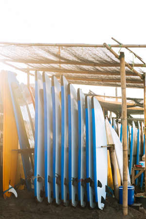 Stack of blue and white color soft surfboards in a stack by ocean.Bali.Indonesia. Surf boards on sandy beach for rent. Surf lessons on Canggu beach.