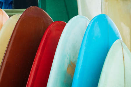Set of colorful surfboard for rent on the beach. Multicolored blue, red, white surf boards different sizes and colors surfing boards on stand, surfboards rental place 版權商用圖片