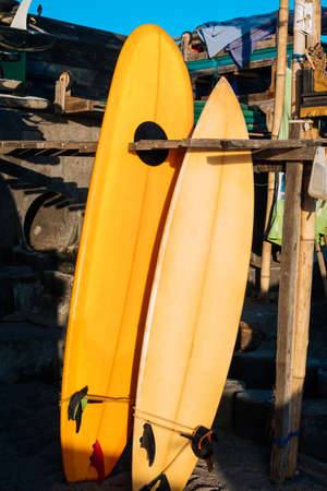 Retro two yellow surfboards for rent on the beach. Multicolored surf boards different sizes on stand in rental place on Bali, Indonesia 版權商用圖片