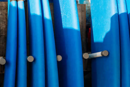 Close up stack of blue color soft surfboards in a stack by ocean.Bali.Indonesia. Surf boards on sandy beach for rent. Surf lessons on Weligama beach, Sri Lanka. 版權商用圖片