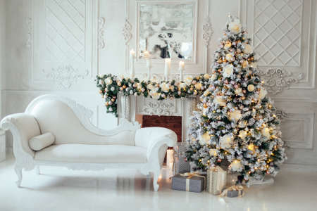 Christmas and New Year decorated luxury interior of living room with fireplace, sofa and New year tree in white classic style. Space for text.