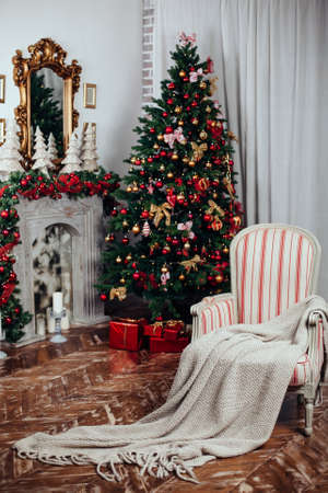 Christmas and New Year decorated interior room with presents and New year tree near fire place in red classic style.