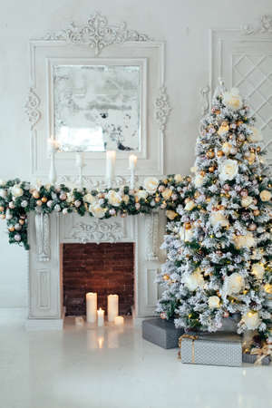 Christmas and New Year decorated luxury interior of living room with fireplace and New year tree in white classic style. Space for text. 版權商用圖片