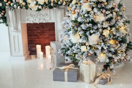 Stacks of Christmas presents in white and grey paper under a Christmas tree decorated white and golden balls near fireplace in living room .New Year interior 版權商用圖片