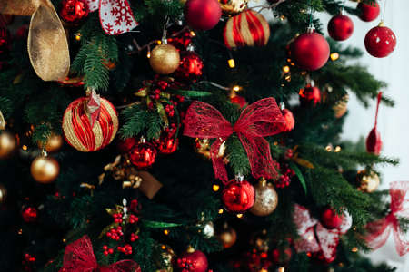Christmas decorations in red and golden color on the branches of fir. Decorated Christmas tree on blurred, sparkling and fairy background 版權商用圖片