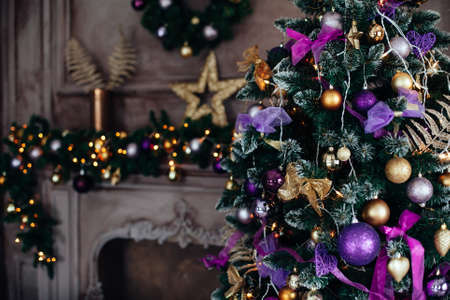 Christmas and New Year decorated luxury interior room with presents and New Year tree near fire place and sofa in violet and golden colors 版權商用圖片