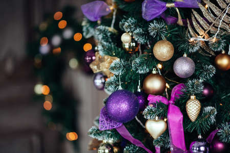 Christmas decorations in violet and golden color on the branches of fir. Decorated Christmas tree on blurred, sparkling and fairy background. New year concept