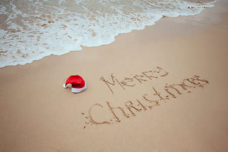 Merry Christmas with Santa red hat written on sand by hand on the tropical beach with ocean. New Year celebration on vacation