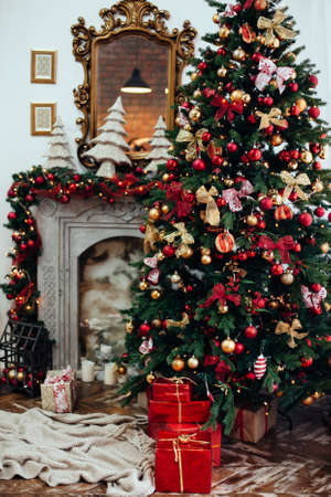 Christmas and New Year decorated interior room with presents and New year tree near fire place in red classic style