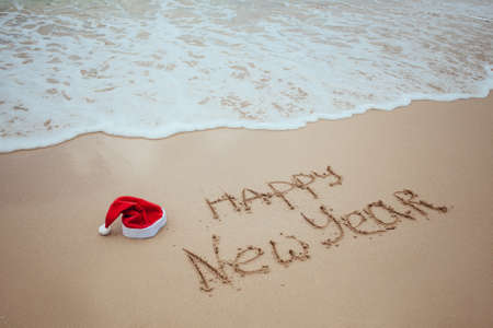 Happy New Year with Santa red hat written on sand by hand on the tropical beach with ocean. Christmas celebration on vacation