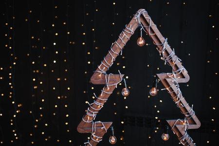 Alternative wooden christmas tree. A handmade New Year tree with light bulb on garland lights black background. Lifestyle trend. Copy space. 版權商用圖片