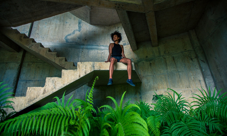 Melanesian pacific islander athlete girl with strong arms after workout sitting at staircase in abandoned building