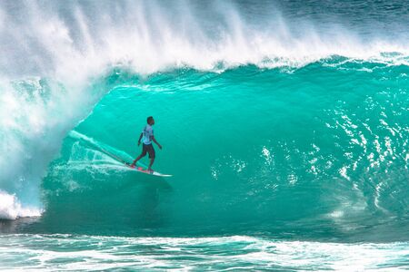 Local surfer riding big green tube section of the wave at Padang Padang beach, Bali, Indonesia