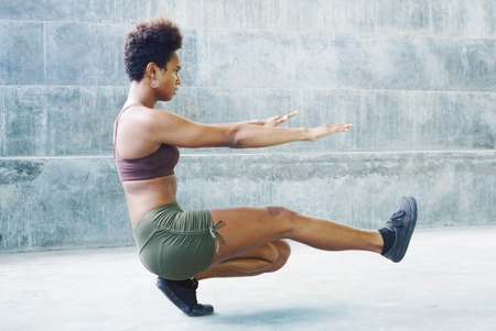 Melanesian pacific islander athlete girl with afro performing exercising routines sitting plank Stock Photo