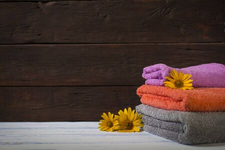 Amazing image of a beautiful bath towel of different colors on a wooden background. Photographed under natural light