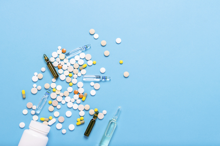 White bottle and multi-colored pills and ampoules with medicines for pricking on a blue background. Concept of pharmaceuticals, medicine, drugs and treatment for diseases. Flat lay, top view.