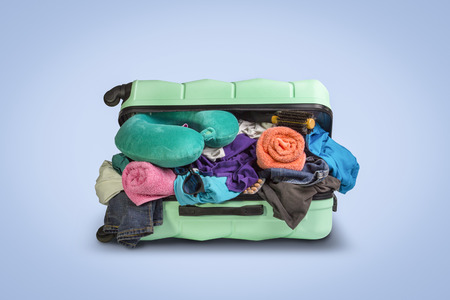 Plastic suitcase with wheels, overflowing things on a blue background. Travel concept, vacation trip, visit to relatives. Stock Photo