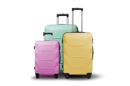 Three multi-colored plastic suitcases on wheels on a white isolated background. Travel concept, vacation trip, visit to relatives.