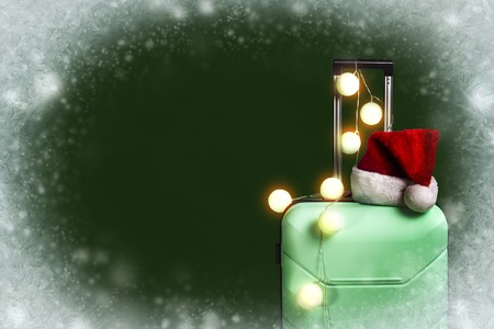 Plastic suitcase, Santa Claus cap and garland on a dark green background with snow. Concept of travel, business trips, trips to visit friends and relatives on Christmas holidays. New Years journey.