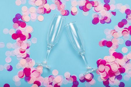 Pink confetti and empty portions for champagne on a blue background. Party and holiday concept. Flat lay, top view. Stock Photo