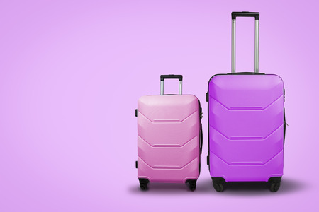 Two Suitcases on wheels on a pink background. Concept of travel, a vacation trip, a visit to relatives. Pink and Green color.