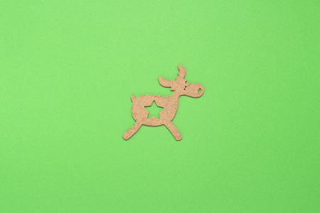 Wooden Christmas toy Deer on a green background. Concept of Merry Christmas and Happy New Year. Minimalistic style. Flat lay, top view.