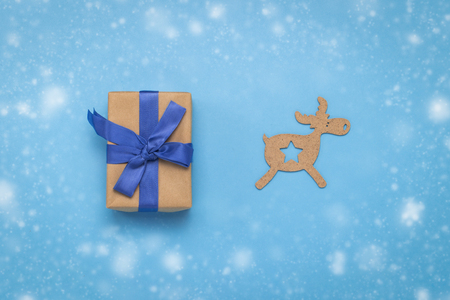 Gift box with a blue ribbon and a Christmas wooden toy Deer on a blue background with the effect of falling snow. The concept of gifts for Christmas and New Year. Flat lay, top view. 스톡 콘텐츠