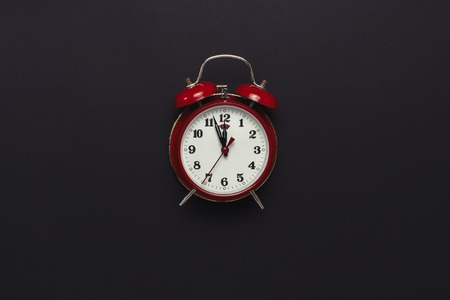 Red retro alarm clock on black background. Minimalism. Flat lay, top view.