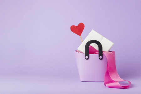 Small plastic bag for shopping, gift boxes, heart on a stick, pink ribbon, violet background. Concept of pre-holiday shopping, sale, Black Friday, Cyber Monday, Valentine's Day. Stock Photo