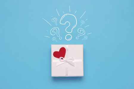 White gift box, red heart and Icon Question mark on a blue background. Minimalistic style. Concept surprise and suspense, a gift from a loved one. Flat lay, top view.