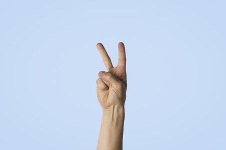 Male hand with two fingers raised against a blue background. Side picture. Peace gesture, greeting.