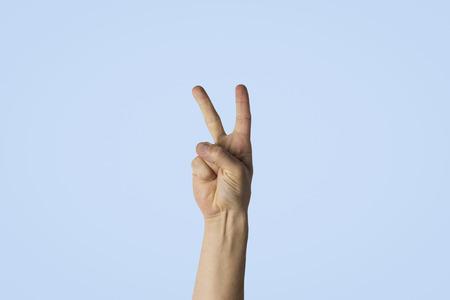 Mano masculina con dos dedos levantados sobre un fondo azul. Imagen lateral. Gesto de paz, saludo. Foto de archivo