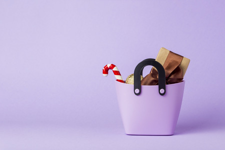Small plastic bag for shopping, gift boxes, heart on a stick, purple background. Concept of pre-holiday shopping, gifts for friends and relatives, Christmas sale, Black Friday, Cyber Monday.