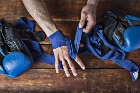 Man bandage boxing tape on his hands before the boxing match on a wooden background. The concept of training for boxing training or fighting. Flat lay, top view. Imagens