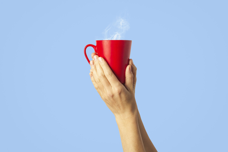 Female hand holding a red cup with hot coffee or tea on a light blue background. Breakfast concept with hot coffee or tea. Reklamní fotografie
