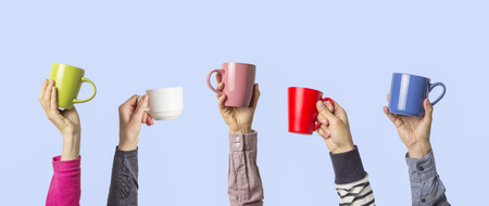 Many different hands holding multi colored cups of coffee on a blue background. Female and male hands. Concept of a friendly team, a coffee break, meeting friends, morning in the team. Banner.