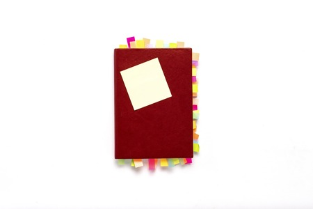 Red diary with stickers on the pages on white background. Concept of a successful business, a lot of meetings and plans for a long period. Flat lay, top view.