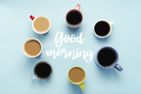 A lot of multi-colored cups of coffee and coffee drinks on a blue background with the text Good morning. Circle shape. Concept breakfast with coffee, coffee with friends. Flat lay, top view. Reklamní fotografie