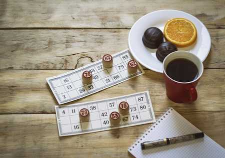 On a wooden table, a bingo game, a notebook and a pen. Cup with coffee, biscuits and orange slice. Flat lay. Stock Photo