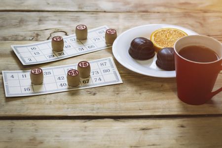 On a wooden bingo table game, a cup with a coffee, a biscuit and an orange slice.