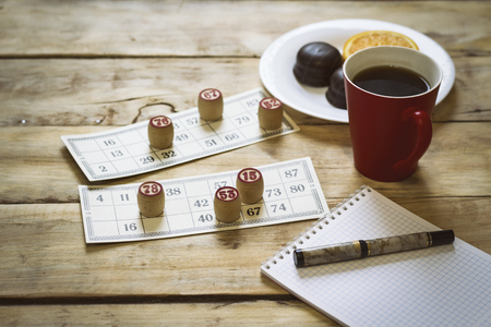 On a wooden table, a bingo game, a notebook and a pen. Cup with coffee, biscuits and orange slice.