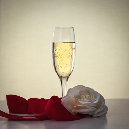 A glass of champagne, a white rose and a red ribbon. Banco de Imagens