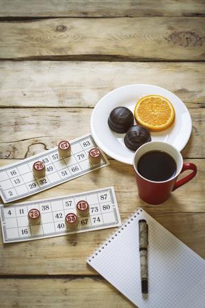 Bingo game cards with bingo on wood background. Added effect. Flat lay.