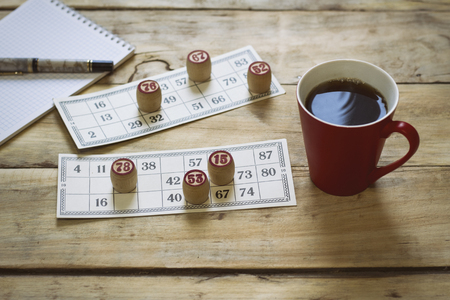 Bingo card with winning chips. Notepad and pen. Cup with coffee. Stock Photo