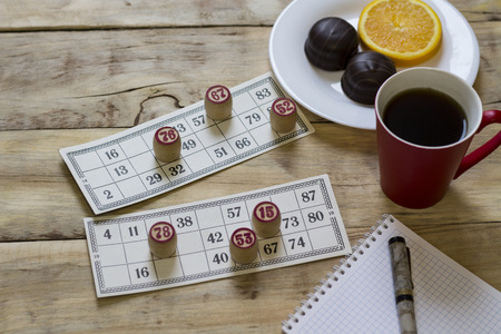 Cards bingo. Tabletop old lotto game with wooden elements. Cup with coffee and biscuit, orange slice. Flat lay.