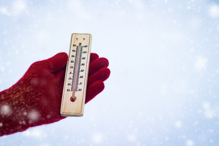 Hand in Red Glove Holds the Thermometer on a Snowy Background.